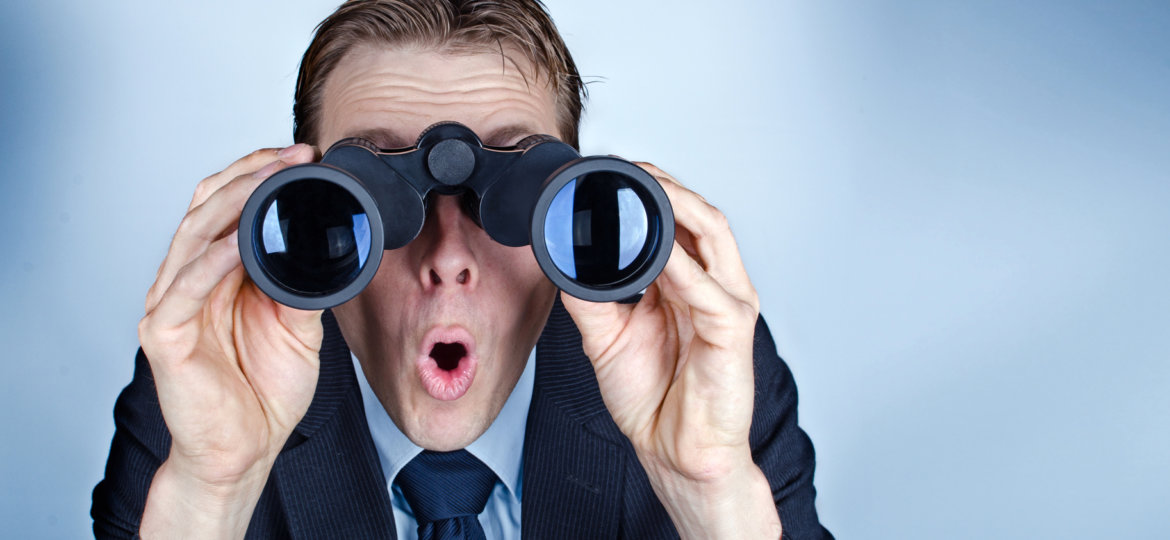 Businessman looking through field glasses or binoculars